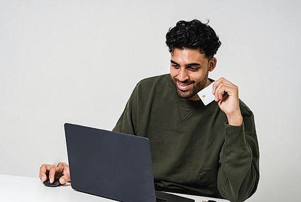De man die aan tafel zit met een zwarte laptop